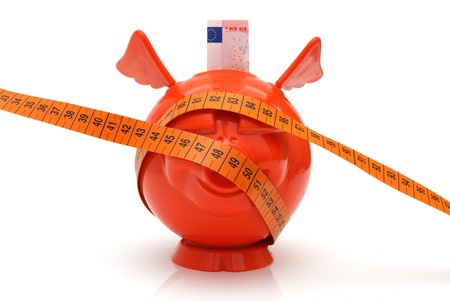 budget restrictions: concept of no money with piggy bank and measuring tape