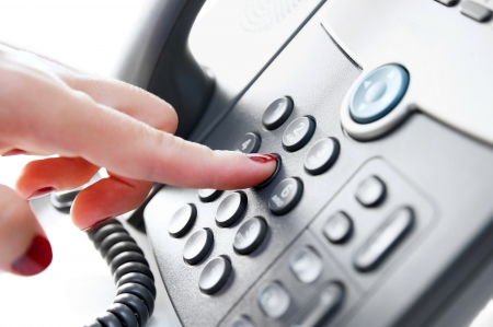 Female hand dialing a phone number Imagens