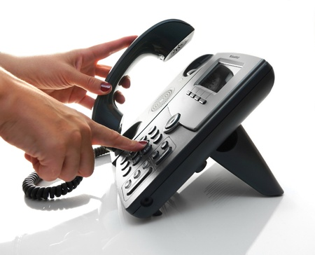 fax: Female hand dialing a phone number with picked up headset Stock Photo