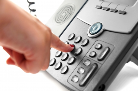 woman hand is dialing a phone number with picked up headset Stock Photo