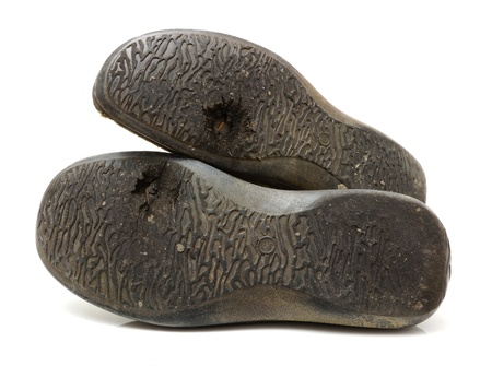 displaced: concept of poor people with old used shoes with  hole isolated
