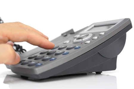 man hand is dialing a phone number with picked up headset photo
