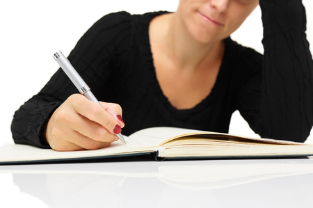 Happy woman writing in her notepad photo