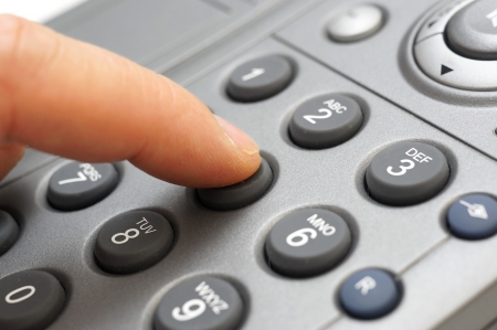 man hand is dialing a telephone number photo