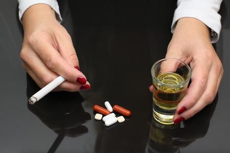 asimiento de la mujer de whisky y cigarrillos en las manos y las drogas en la mesa