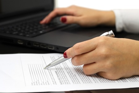 validating: close up of female business hands working on  document and laptop Stock Photo