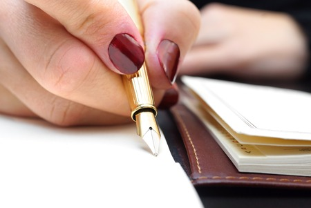 pointed arm: Woman is writing in notepad Stock Photo