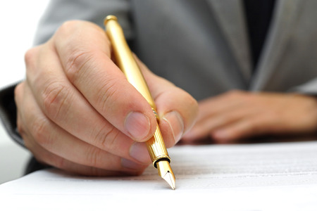 fulfilling: businessman is fulfilling and signing contract with fountain pen