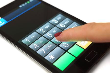 女性が携帯電話のタッチ スクリーン携帯電話をダイヤルします。