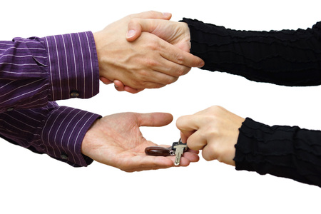 house key: woman receiving a handshake and a house key at the same time