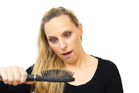 calvicie: peine del pelo pérdida por tenencia mano de las mujeres Foto de archivo