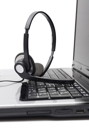 telephone headsets: Laptop computer with headset on keyboard Stock Photo