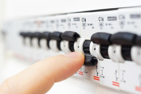 electrical cable: man turning off the fusebox