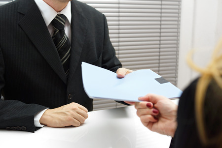 Employment interview with female applicant handing over a file containing her curriculum vitae to the businessman Stock Photo - 25963023