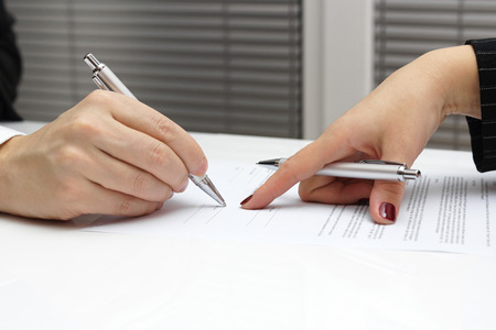 businesswoman point with finger on paper to sign up contract photo