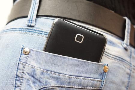 hand in pocket: mobile phone in woman jeans pocket