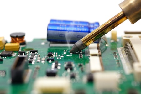 Electrical Engineer is soldering on printed circuit board photo