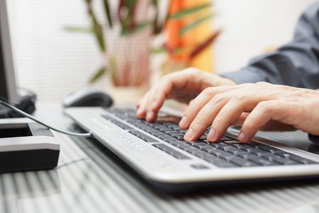 man is aan het typen op het toetsenbord thuis