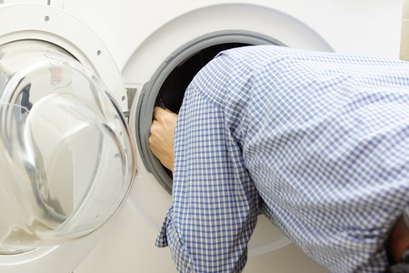handyman repairing a washing machine photo