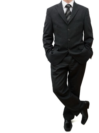 business man standing with legs crossed and both hands in his pockets Stock Photo