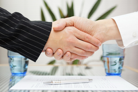 settlements: businessman and businesswoman shaking hands over signed contract