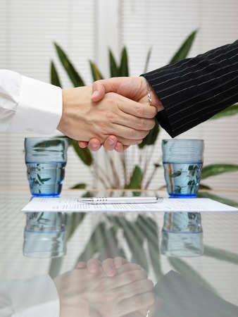 legal services: man and woman shaking hands over signed insurance
