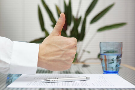 thumbs up gesture over signed application photo