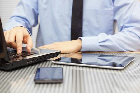 ノート パソコンに入力し、タブレットを見て事務所にスーツのビジネスマン