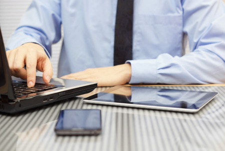 empresario de traje en la oficina escribiendo en la computadora portátil y mirando la tableta Foto de archivo