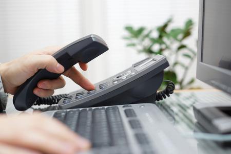 ビジネスマンがオフィスで電話番号をダイヤルします。