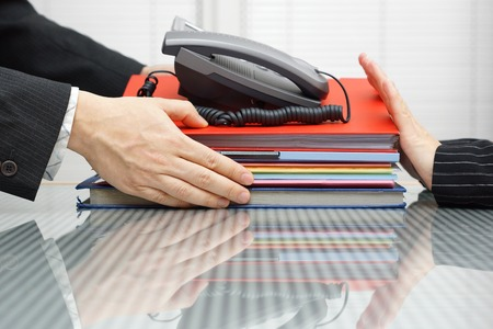 office force: businessman is receiving files,folders  and telephone from coworker