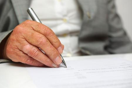 ドキュメントに署名するそれ以上の年齢の女性 写真素材