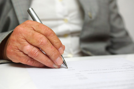 older woman signing the document Stock fotó