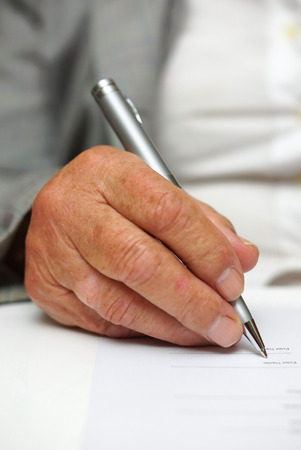 older woman signing the document photo
