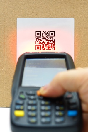 scanning QR code  label on the carton with laser Stock Photo