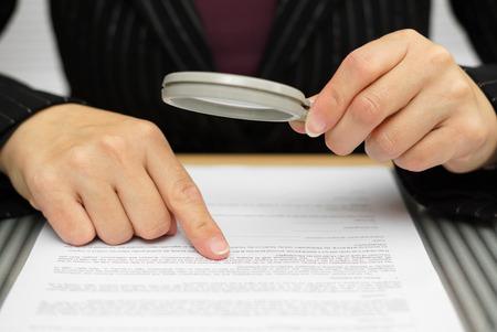 revisando documentos: Empresaria que mira a través de una lupa para contratar Foto de archivo