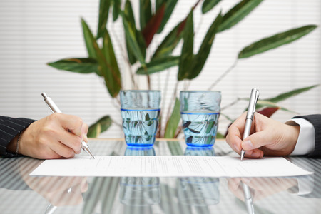 man and woman signing document with divorce or prenuptial agreement