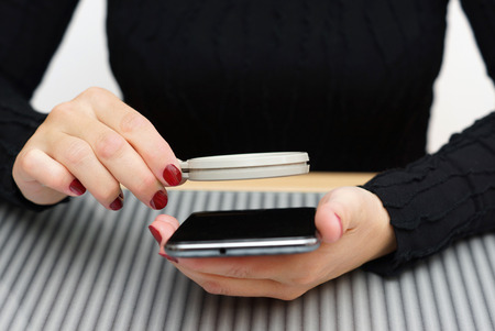 woman read small text on mobile phone with magnifying glass photo