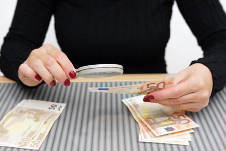 dinero falso: mujer está mirando a través de una lente de aumento para la falsificación de dinero