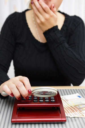 cant: woman watching sum on calculator with magnifying glass and cant believe numbers on it