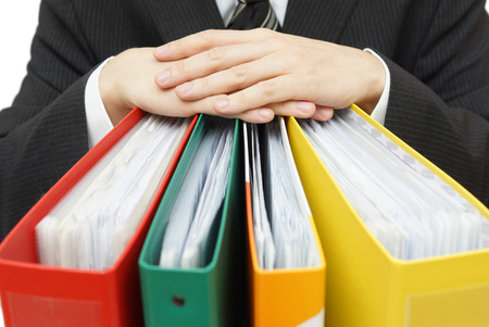 Midsection of businessman with binders at office photo