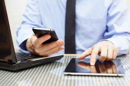aussi: homme d'affaires travaille sur tablette et t�l�phone intelligent � l'aide dans le bureau avec un ordinateur portable