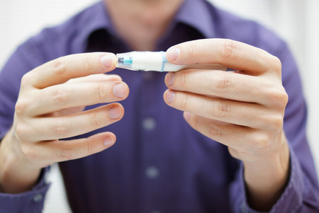 blood sugar level: Closeup of young man using checking level of sugar in blood