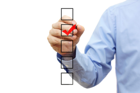 tasks: Young businessman checking mark on checklist with marker. Isolated on white.
