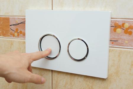 flushing: finger pushing button for  flushing toilet Stock Photo