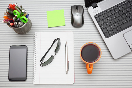 office desk with laptop with business accessories and cup of tea photo