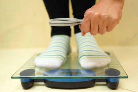 exaggerate: woman feet on weighing scales looking weight over magnifying glass  exaggerate with weight loss concept