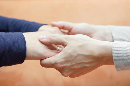 Mannelijke handen die vriendin handen zorg en liefde concept