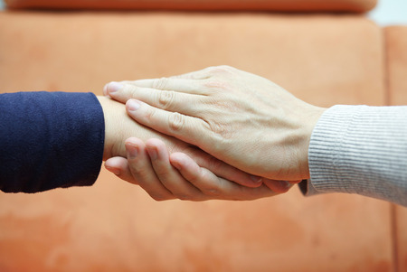 empatia: manos del hombre la celebración de mano de la mujer de los dos lados compasión y preocupación concepto