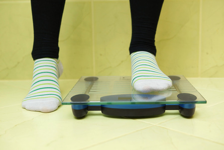 A woman wants to weigh and stands on the scales photo
